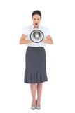 Gritaria irritada da mulher de negócios em seu megafone Fotografia de Stock