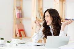 Gritaria irritada da mulher de negócios no telefone no escritório imagem de stock