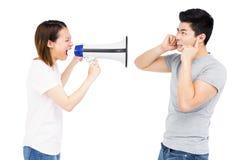 Gritaria irritada da mulher no homem novo no altifalante de chifre Imagens de Stock