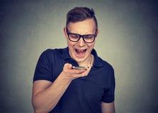 Gritaria irritada nova do homem no smartphone fotos de stock