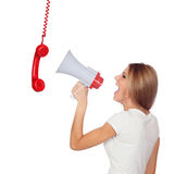 Gritaria loura da mulher através de um telefone que pendura com um megafone Imagens de Stock Royalty Free