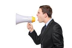 Gritaria nova do homem de negócios em um megafone Fotografia de Stock Royalty Free