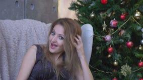 Gritaria surpreendida da jovem mulher sobre o fundo da árvore de Natal olhando a câmera video estoque