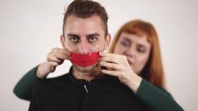 Griterío agresiva enojada del hombre y cinta joven de la mujer que cuida su boca con el papeleo para calmarlo abajo almacen de video