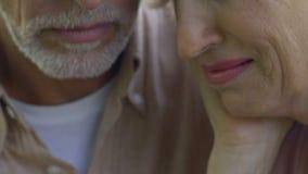 Griterío de la mujer mayor, hombre mayor abrazándola cuidadosamente para apoyar y para calmar abajo almacen de metraje de vídeo