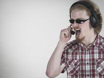 Griterío de los auriculares del hombre del videojugador que lleva Foto de archivo