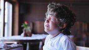 Griterío del muchacho Grito trastornado del pequeño niño en el café almacen de metraje de vídeo