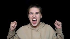 Griterío enojado de la mujer joven aislado en fondo negro Hembra enfurecida en fondo negro que grita, concepto de la locura foto de archivo