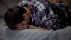 Griterío masculino devastado en cama, esposa y la pérdida de los niños, subrayada y deprimida imágenes de archivo libres de regalías