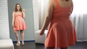 Griterío regordete de la muchacha, sosteniendo los anillos de espuma delante del espejo infelices con su aspecto fotografía de archivo