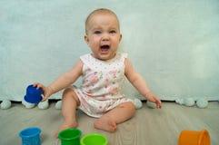 Grito del bebé con los juguetes histerical del juego de la cólera Fotografía de archivo
