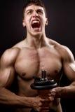 Grito del bodybuilder muscular de gran alcance imagenes de archivo
