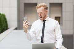 Grito del hombre de negocios del jengibre en teléfono elegante en la charla video Fotografía de archivo libre de regalías