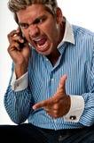 Grito del hombre en un teléfono Imagen de archivo libre de regalías