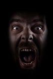 Grito do homem assustador scared na obscuridade Imagens de Stock Royalty Free