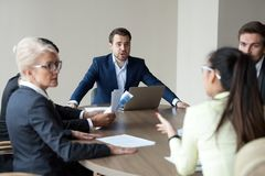 Grito ejecutivo enojado teniendo desacuerdo con el empleado en la reunión de grupo imágenes de archivo libres de regalías