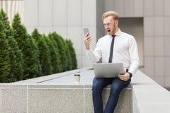 Grito loco del hombre de negocios del jengibre en teléfono elegante Foto de archivo libre de regalías