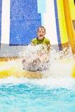 Gritos del muchacho mientras que desliza abajo el tobogán acuático Imagen de archivo