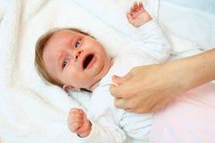 Gritos recién nacidos cuando lo visten Imágenes de archivo libres de regalías