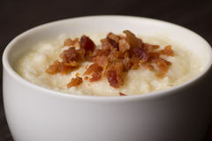 Grits topped with bacon. Warm grits with butter, topped with bacon Royalty Free Stock Image