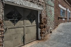 Gritty Alleyway in Todos Santos, Mexico. Crumbling Red Brick and Ornate Doors in a Mexican Alleyway make for a Moody and Gritty Scene Stock Images