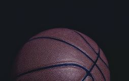 Grungy closeup of half a basketball on a black background royalty free stock image