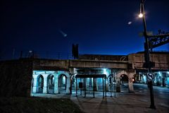 Gritty dark Chicago city street intersection at night. Gritty dark Chicago city street intersection under industrial train bridge viaduct tunnel with a CTA bus Royalty Free Stock Photography