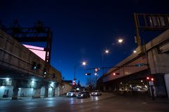 Gritty dark Chicago city street intersection at night. Gritty dark Chicago city street intersection under industrial train bridge viaduct tunnel and highway Stock Photo