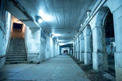 Gritty dark Chicago city street at night. Gritty dark Chicago city street under industrial bridge viaduct tunnel with a stairway to Metra train station at night Royalty Free Stock Images