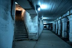 Gritty dark Chicago city street with stairs at night. Gritty dark Chicago city street under industrial bridge viaduct tunnel with a stairway to Metra train Stock Photo