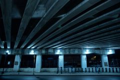 Gritty dark Chicago highway bridge at night. Gritty dark Chicago highway bridge and city street with a bicycle stand at night Stock Photos