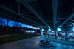 Gritty dark Chicago highway bridge underpass at night. Gritty dark Chicago highway bridge underpass and city street with traffic and a bench at night Stock Image
