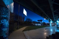Gritty dark Chicago highway bridge with graffiti at night. Gritty dark Chicago highway bridge underpass with graffiti and billboards at night Stock Photography
