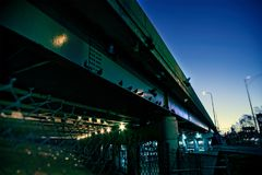 Gritty dark Chicago highway bridge underpass. Gritty dark Chicago highway bridge underpass with pigeons near a fence during sunrise Royalty Free Stock Photos