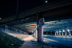 Gritty dark city highway bridge street underpass at night Stock Photography