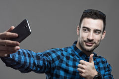 Gritty desaturated high contrast portrait of young happy man taking selfie with thumbs up. Gesture over gray studio background Royalty Free Stock Photography