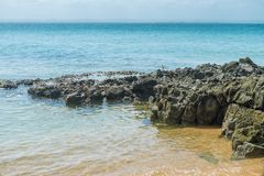 Gritty rocks by the shoreline with small  pools. Gritty rocks by the shoreline with small salt water pools Stock Photography
