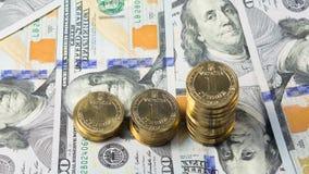 Grivna ucraniano de la moneda (hryvnia, 1 UAH) en el fondo de 100 cuentas de los E.E.U.U. del dólar (100 USD) - demostración del  Fotos de archivo libres de regalías
