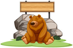 Grizzly bear sitting next to the sign Stock Photos