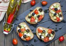 Grka stylowy crostini z feta serem, pomidorami, ogórkiem, oliwkami i ziele, Obrazy Royalty Free
