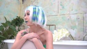 Grl en peluca se sienta solamente en cuarto de baño almacen de metraje de vídeo