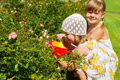 Grls watering flowers Royalty Free Stock Image