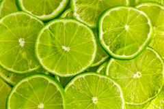 Grön bakgrund med limefruktskivor Arkivbilder