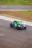 Grön bil med purpurfärgade stänkskärmar Arkivbild