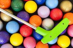 Grön golfputter med färgrika bollar Arkivbilder