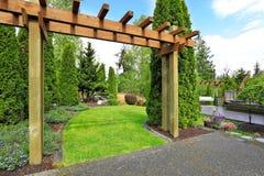 Grön gräsmatta med antika bänkar Trädgårds- ingång Arkivfoto