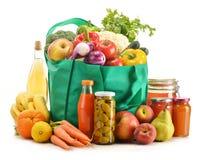 Grön shoppingpåse med livsmedelsbutikprodukter på vit Royaltyfri Foto