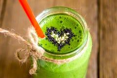 Grön smoothie med hjärta av frö Arkivfoton