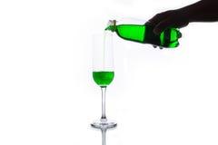 Grön sodavatten som häller in i exponeringsglas Arkivfoto