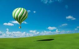Grün-weißer Heißluft-Ballon im blauen Himmel Lizenzfreie Stockfotos
